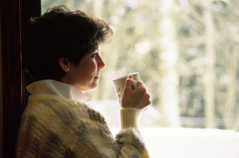 Woman sitting drinking tea looking out the window